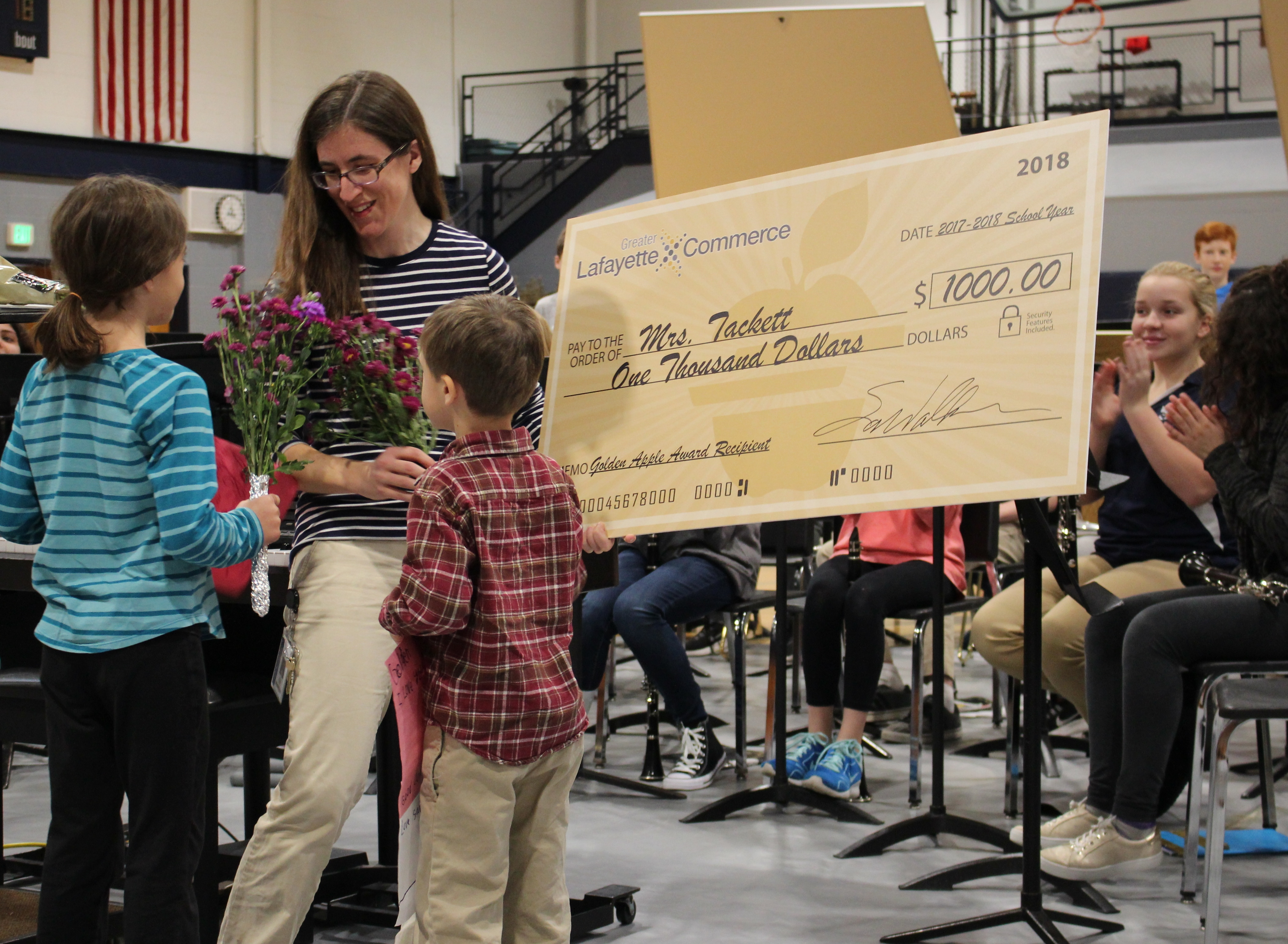 Katherine Tackett receives flowers from her children when she learns she won a Golden Apple award.