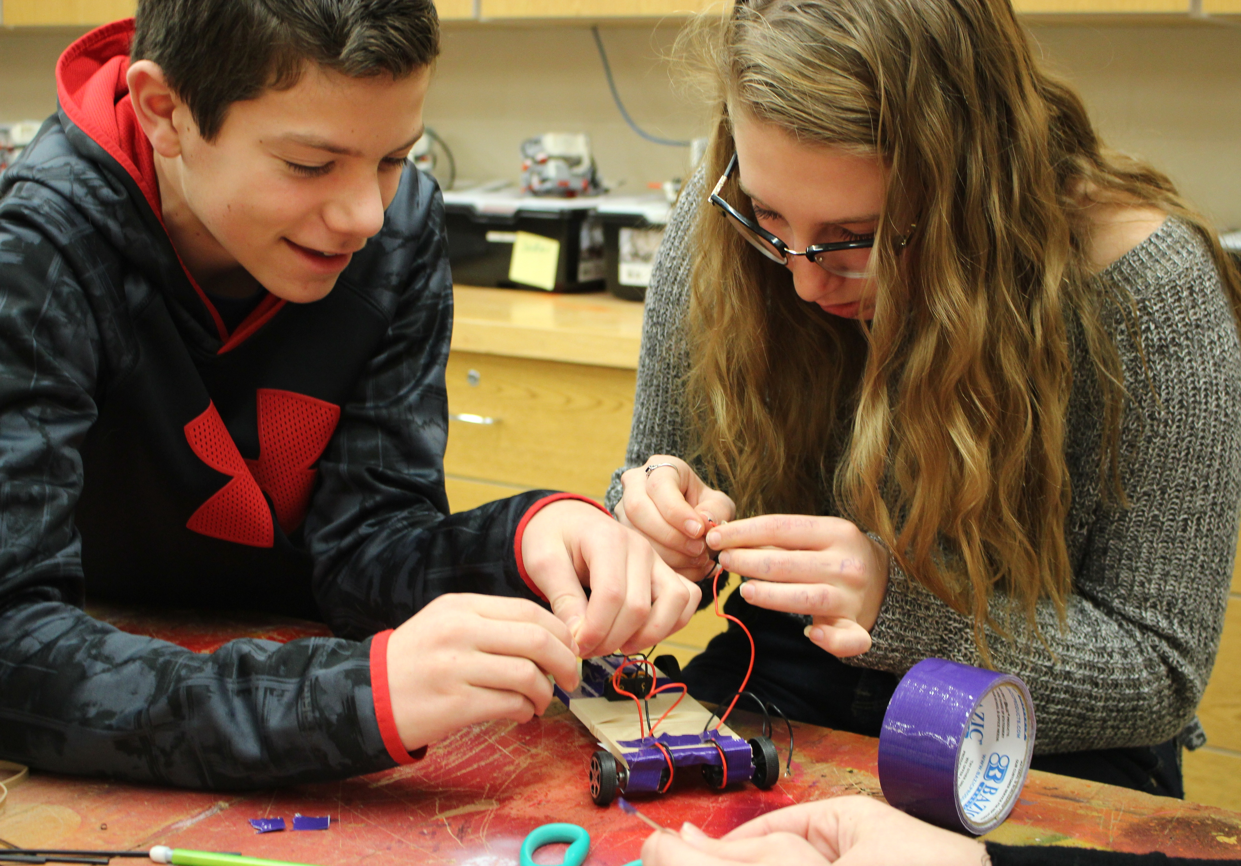 Two students work on the wiring for the car
