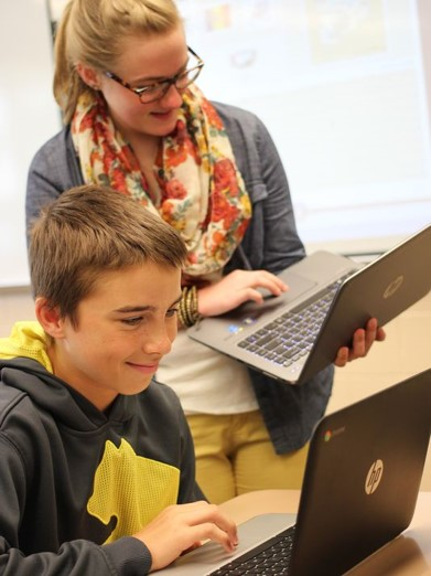Teacher working with student on chromebook